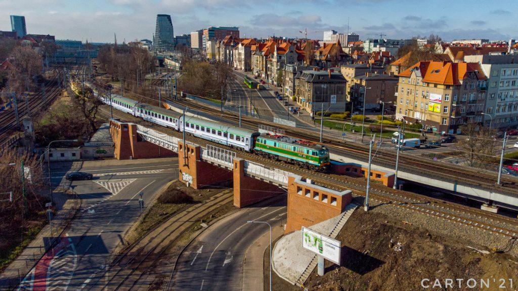 """Elektrowóz EP07-376 PKP Intercity z pociągiem """"Gwarek"""" wyjeżdża z Poznania."""